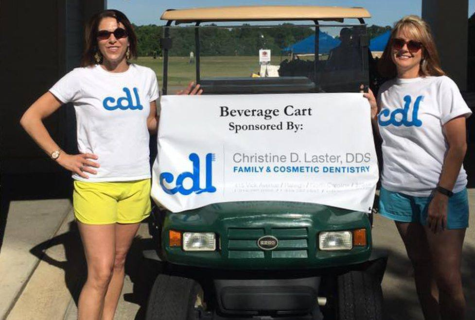 Two team members by a golf cart at community event