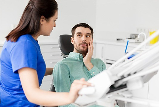 Man in dental chair holding cheek