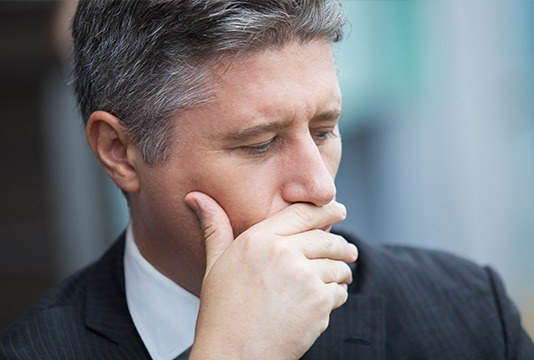 Man in business suit covering his mouth