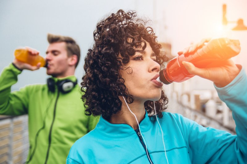 Man and woman drinking a sports drink