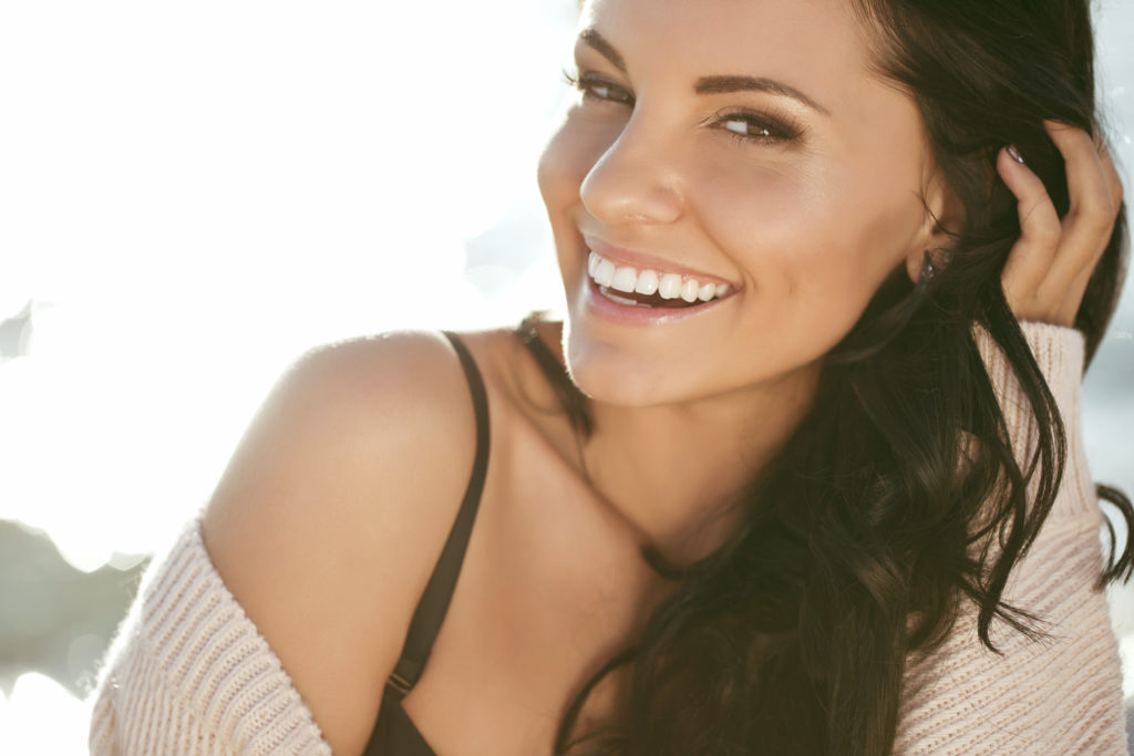 Woman showing off her straight, white smile