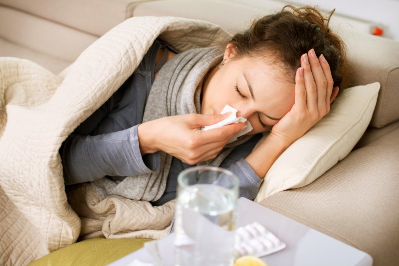 Closeup of woman with a cold resting on couch