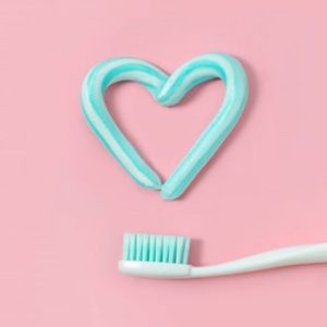 A heart shape drawn with toothpaste sitting above a toothbrush against a pink background
